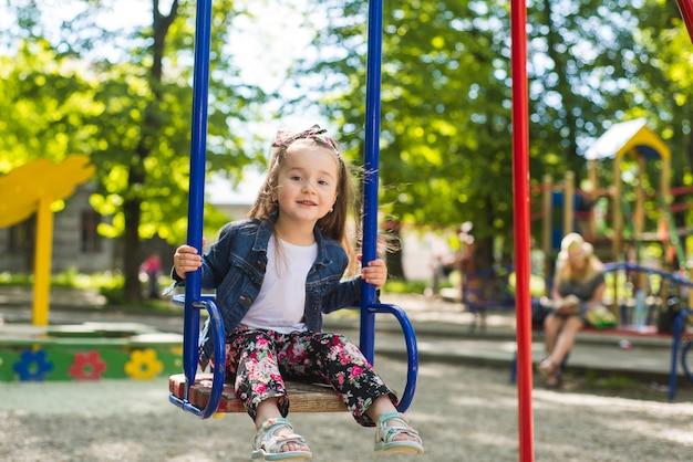 公園の屋外の子供の遊び場でブランコに乗って幸せな少女