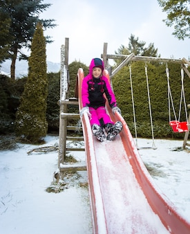Счастливая маленькая девочка, катающаяся с горки на детской площадке в снежный день