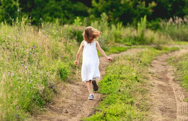 屋外の地上パスに沿って実行している幸せな女の子。背面図