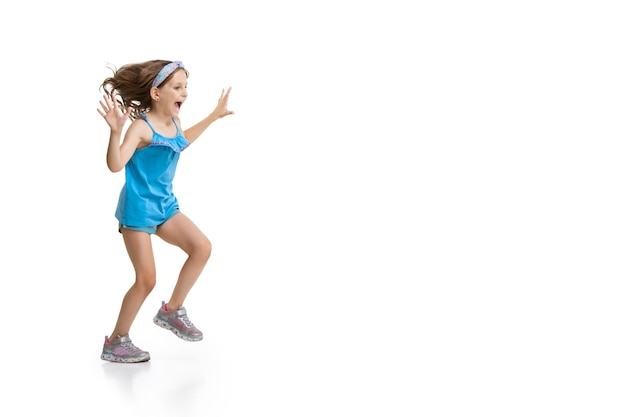 Happy little girl running and jumping on white wall