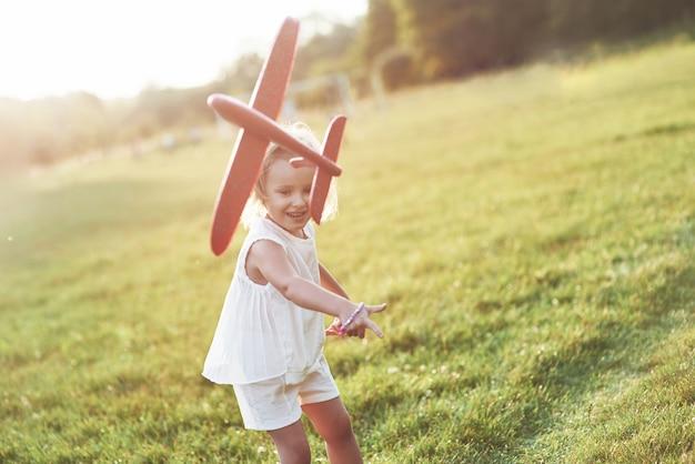 Счастливая маленькая девочка, бегущая по полю с красным игрушечным самолетиком в руках
