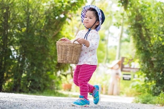 Happy little girl running with basket in the garden farm