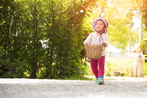 庭園のバスケットで走っている幸せな少女 Premium写真