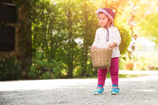 庭園のバスケットで走っている幸せな少女