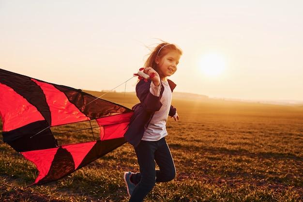 Sunrishe 시간에 아름다운 필드에 손에 연을 실행하는 행복 한 어린 소녀