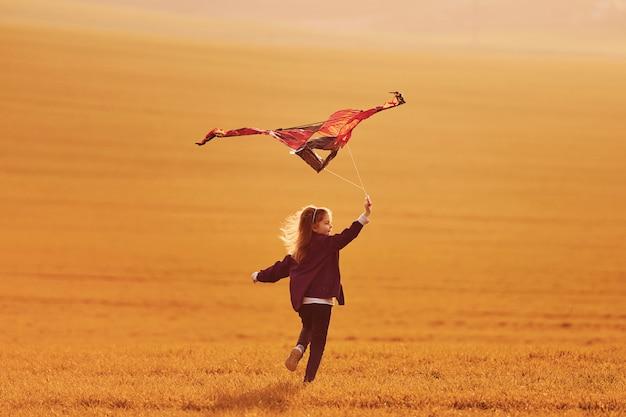 아름 다운 필드에 손에 연을 실행하는 행복 한 어린 소녀