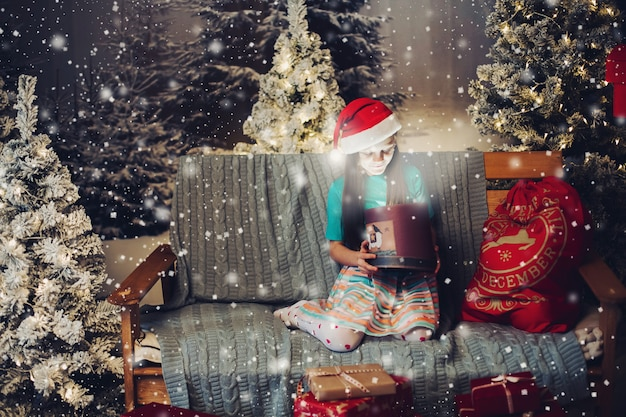 Happy little girl in santa claus hat with present on couch.