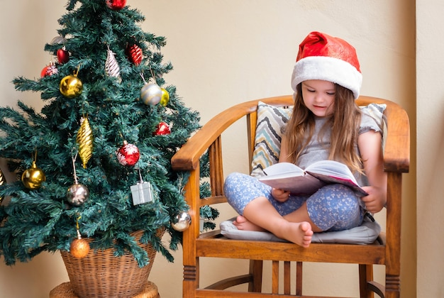 Happy little girl in the santa hat reads a book while sitting in the chair near christmas tree