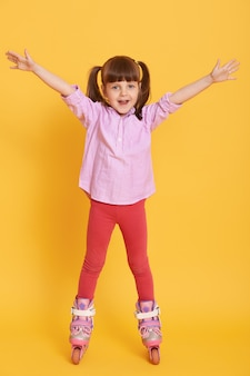 Happy little girl in shirt and leggins with roller skates posing indoors with hands up