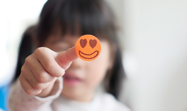Happy little girl showing a smiley sticker