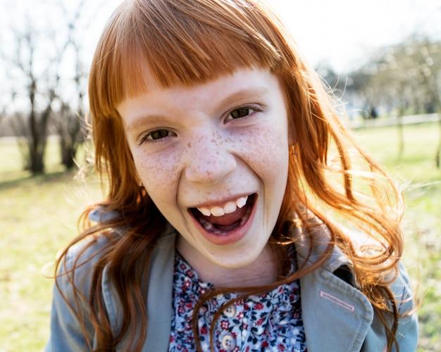 혀를 보여주는 행복 한 어린 소녀를 닫습니다