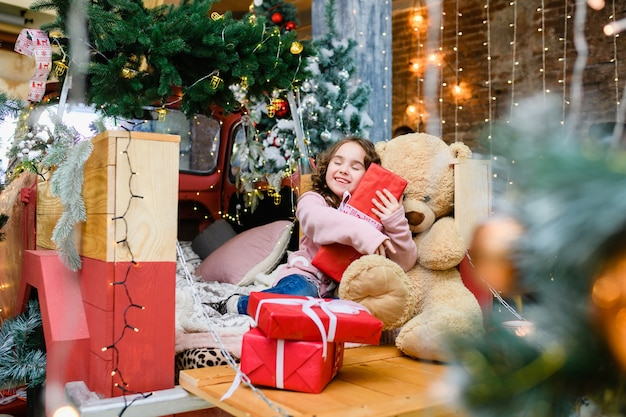 幸せな少女は、飾られたクリスマスと新年のモミの木とテディベアの近くに座って、笑顔で大きな赤いプレゼントボックスを保持します