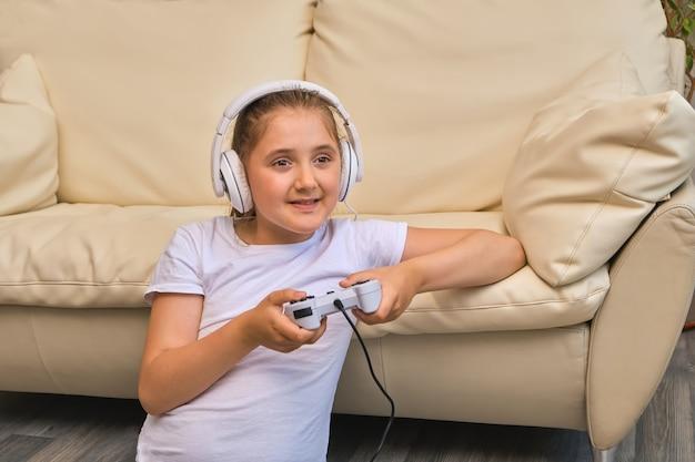 幸せな女の子は自宅のソファでリラックスして座ってオンラインビデオゲームを楽しんでください。ビデオゲームでバーチャルリアリティに関わる大喜びの小さなゲーマー