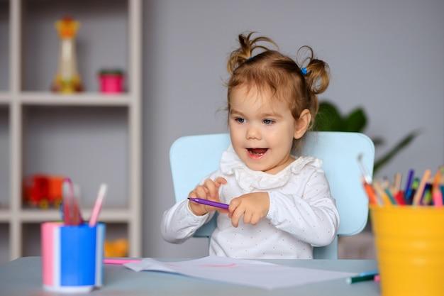 Счастливая маленькая девочка сидит за столом и рисует на бумаге цветными карандашами