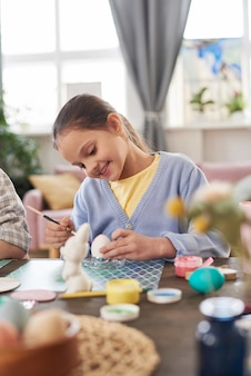 Счастливая маленькая девочка, сидящая за столом, расписывающая и украшающая яйца на пасху дома