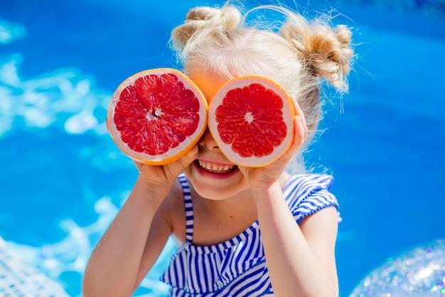 Счастливая маленькая девочка сидит у бассейна летом и пьет лимонад