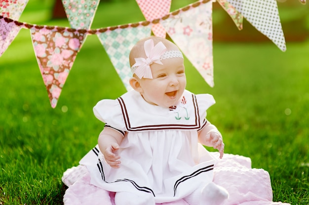 Happy little girl sitting on grass with flags