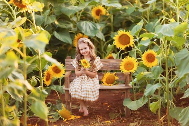 夕日の光線の下で咲くひまわりの中でベンチに座って幸せな少女