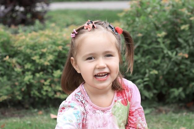 夏の日に芝生に座っている幸せな少女