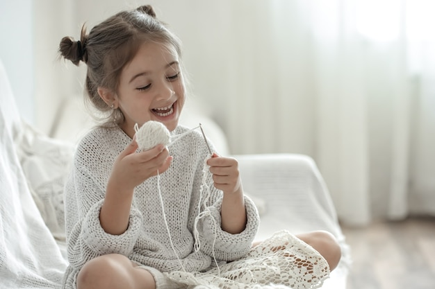 Happy little girl sitting on the sofa and learning to knit, home leisure concept.