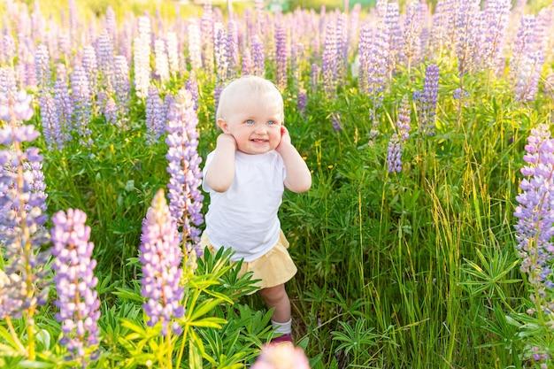 야외에서 웃 고 행복 한 어린 소녀입니다. 아름 다운 금발의 어린 아기 소녀 개화 야생 꽃 녹색 배경으로 여름 필드에 쉬고 있습니다. 무료 행복한 아이, 어린 시절 개념. 긍정적인 유아 아이