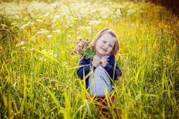야외 웃 고 행복 한 어린 소녀입니다. 피는 야생 꽃 녹색 배경으로 여름 필드에 쉬고 아름 다운 금발 어린 아기 소녀