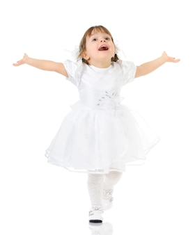 Happy little girl smiling and posing in white dress and shoes, hands spread apart, light background for a photo in full length