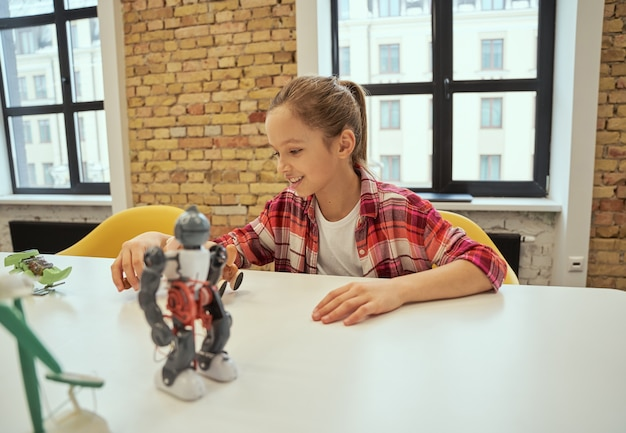 테이블에 앉아 기술 장난감을 가지고 노는 동안 웃고 있는 행복한 어린 소녀