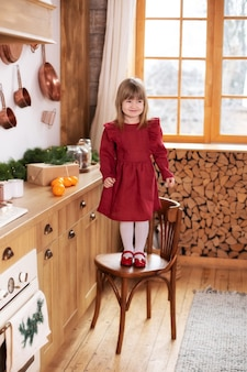 Happy little girl stand on chair in kitchen in decorations with christmas tree and gift