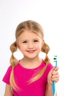Happy little girl standing with toothbrush isolated on white.