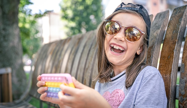 Happy little girl in sunglasses with a smartphone in a trendy case pop it.