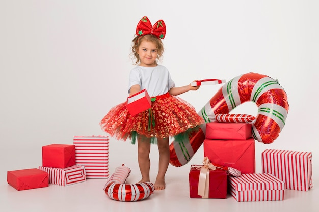 Счастливая маленькая девочка в окружении рождественских элементов