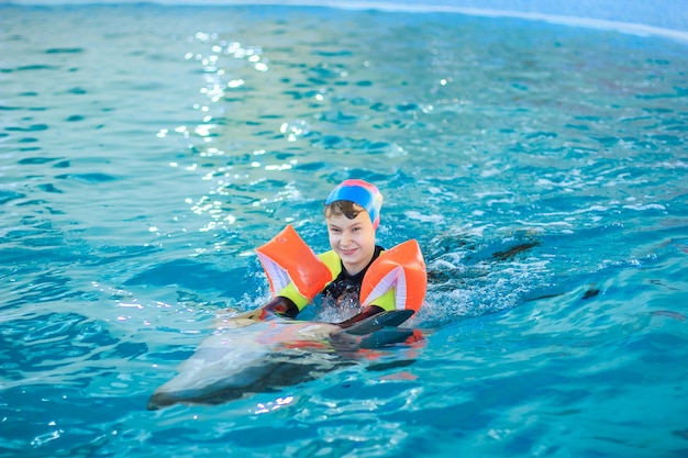 Happy little girl swimming with dolphins in dolphinarium.