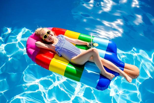 Счастливая маленькая девочка плавает в бассейне летом на матрасе в виде мороженого.