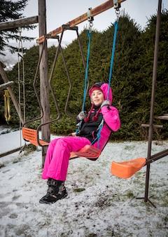 Счастливая маленькая девочка качается на детской площадке в снежный зимний день