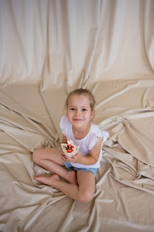 Happy little girl in a t-shirt and shorts sits and holds a festive cupcake with strawberries and a candle on a beige background with a copy of the space