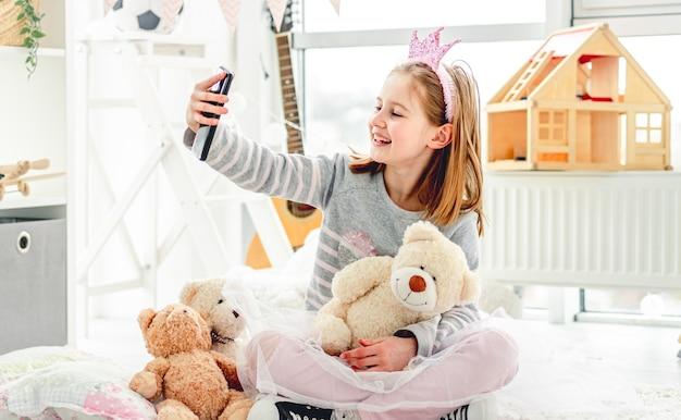 Счастливая маленькая девочка, делающая фото с игрушками в милой игровой комнате