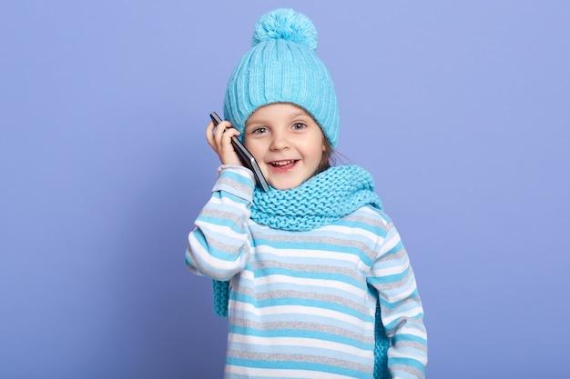 Happy little girl talking to her mother via modern cell phone against blue studio