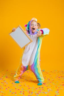 A happy little girl in a unicorn kigurumi holds an empty board for text on a yellow wall
