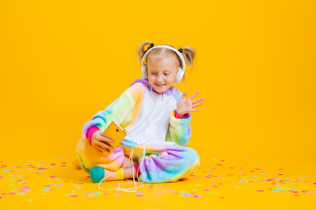 A happy little girl in a unicorn kigurumi sits on a yellow surface taking a selfie
