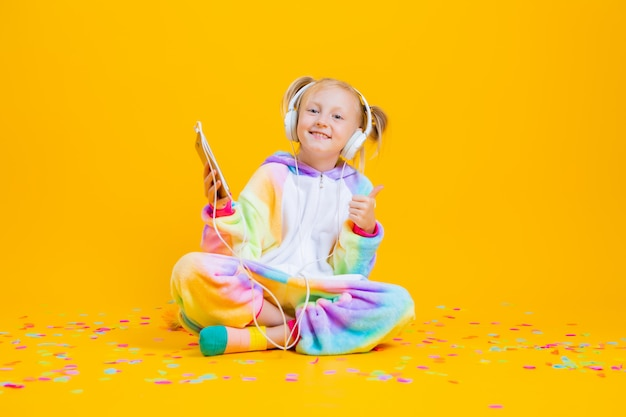 A happy little girl in a unicorn kigurumi sits on a yellow surface