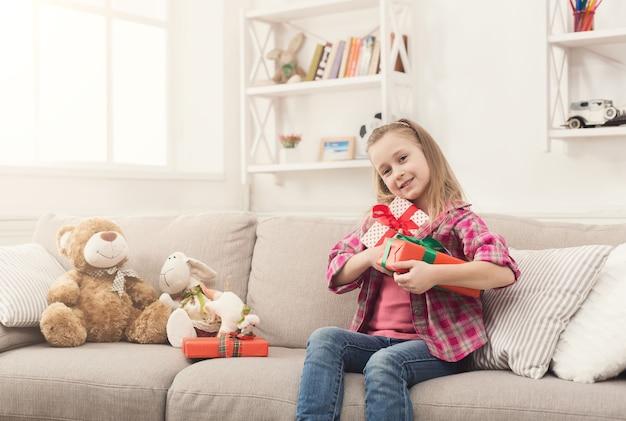 선물을 풀고 행복 한 어린 소녀입니다. 아름다운 아이는 집에 있는 소파에서 선물을 풉니다. 축제 개념입니다. 크리스마스 또는 생일 파티, 복사 공간