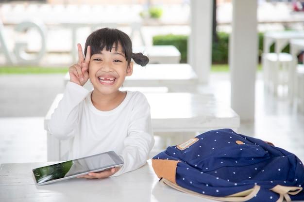 家でタブレットを使用して、現代のデバイス画面を見て、ガジェットを楽しんで、漫画を見て、ゲームをしているかわいい就学前の子供の子供を笑顔で幸せな女の子