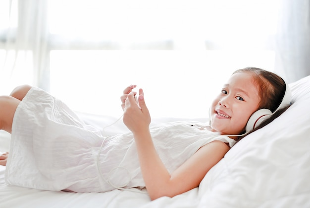 Happy little girl using headphones listen music by smartphone while lying on bed at home.