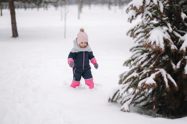 Счастливая маленькая девочка гуляет в парке на снегу.