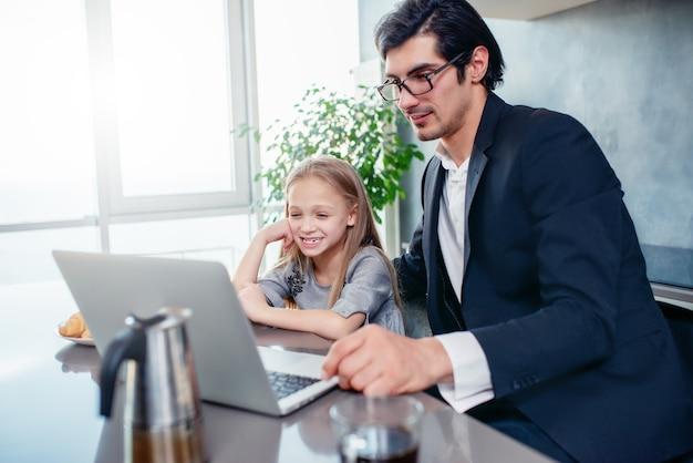 彼女の父と一緒にコンピューターで映画を見ている幸せな少女
