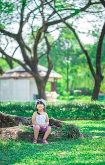 Happy little girl wear hat sitting on tree root in the park