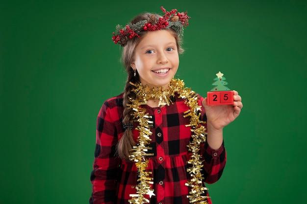 首に見掛け倒しのチェックドレスでクリスマスリースを身に着けている幸せな少女は、顔に笑顔でクリスマスの日付とおもちゃのキューブを保持しています