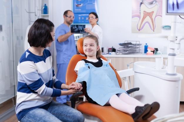 歯の検査を待っている親の手を保持している歯科医院で歯科よだれかけを着ている幸せな少女。歯の間に母親と一緒にいる子供は、椅子に座っている口内検査で診察します。