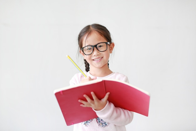 Happy little girl wearing eyeglasses and hold a book and write with pencil on white.